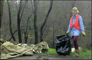 A volunteer with a trash bag picks up trash along the side of a road