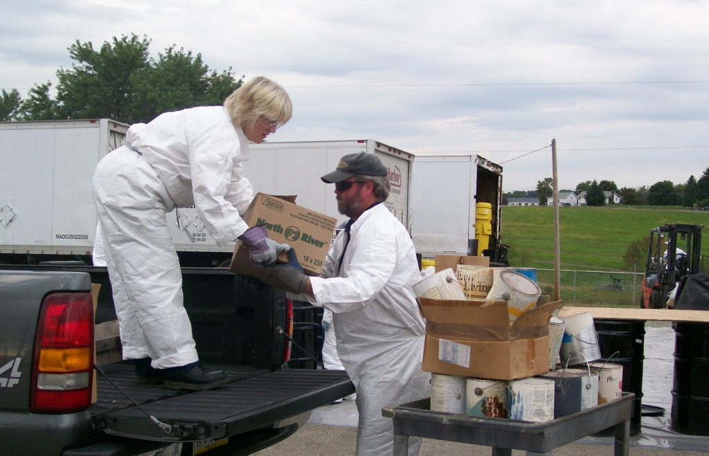 Loading boxes of paint cans onto a truck during a recycling event